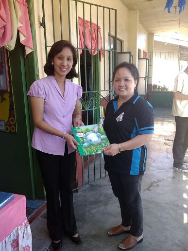 Ms. Mactal, handling books to the OIC of the Library